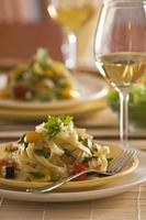 Colorful pasta dish, accompanied by a glass of white wine