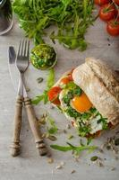Ciabatta with fried egg, tomatoes and pesto photo