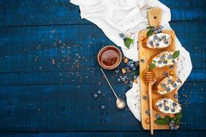Sandwiches with soft cheese and blueberries on a wooden background.