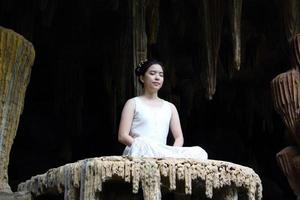 Asian woman does meditation in cave