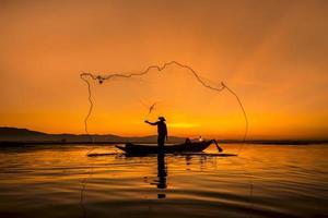 Pescador del lago bangpra en acción cuando pesca, Tailandia. foto