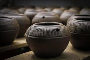 Clay pots with carved motifs in a row