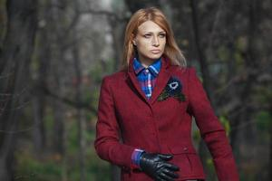 Beautiful blonde woman in tweed jacket in autumn forest