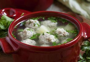 Soup with meatballs in red pots