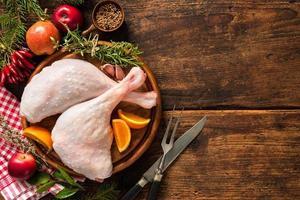 Raw goose legs with herbs on cutting board