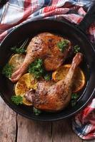 Roast duck leg with oranges and parsley vertical top view