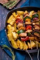 Grilled meat and vegetable kebabs and baked potatoes on pan