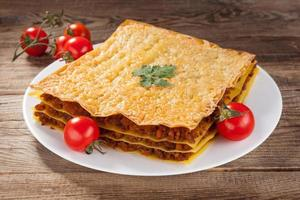 Lasagna and cherry tomatoes on a table of old boards