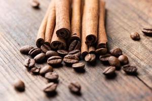 Palitos de canela y café sobre fondo de madera macro foto