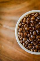 Coffee beans in cup on grunge wooden background