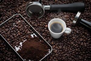 taza de café exprés caliente y granos de café tostados.
