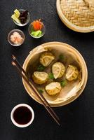 Dim sum dumplings in steamer and ingredients top view
