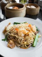fideos fritos con camarones y calamares en plato blanco