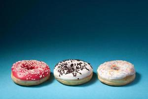 three donuts with color icing isolated on blue background