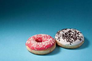 two donuts with red and white icing isolated on blue