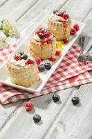 Puff pastries with vanilla-icecream and cream, blueberries and raspberries