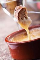 Nahaufnahme von knusprigem Brot in eine Schüssel Fondue getaucht