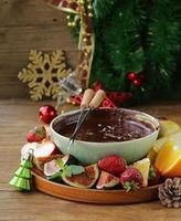Christmas dessert chocolate fondue with various fruits photo
