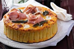 Pasta pie with cheese sauce and sage photo