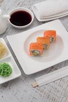 sushi sur une plaque blanche sur fond de bois vintage.