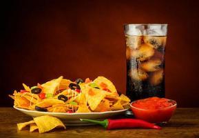 nachos, salsa dip and cola drink