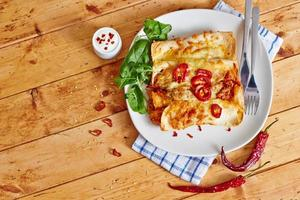 Enchiladas dish with red hot chili top view photo