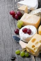 assortment of cheeses and grapes on a wooden board