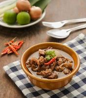 Thai beef curry in brown bowl on wood table. photo