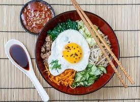 bibimbap in a bowl with sauces on bamboo mat, korean