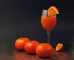 vaso de jugo de naranja con naranjas