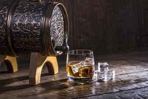 Barrel and a glass of whiskey and ice