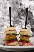 Canape with red fish , pancakes, onion, black caviar in white photo