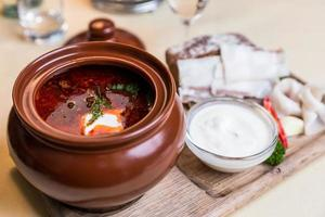 Restourant serving dish - soup on wooden board on table photo