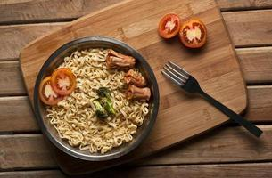 noodles with tomato and sausage in stainless steel bowl photo