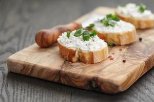crunchy baguette slices with cream cheese and green onion photo