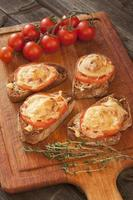 Delicious bruschetta with tomatoes on cutting board photo