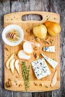 Blue cheese with pear, nuts and honey top view