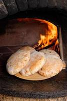 Fresh bread in front of the oven fire photo