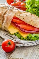 Summer sandwich with ham, cheese, salad and tomatoes, onion, juice photo
