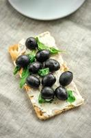 Crispbread with fromage, olives and herbs photo