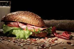 sanduíche em uma mesa de madeira com fatias de bacon