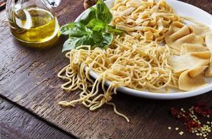 pasta casera y aceite de oliva en la mesa de madera foto
