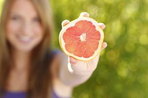 Woman holding a slice of grape fruit
