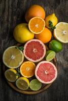 Fresh citrus fruits on rustic wooden background, top view