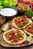 tortillas with chili con carne and tomato salsa on board