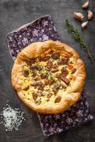 Caramelized garlic tart with goat cheese on dark wooden backgrou