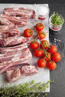 costine di maiale crude con pomodorini ed erbe
