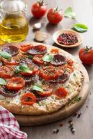 Italian food - pizza with salami and tomatoes, vertical