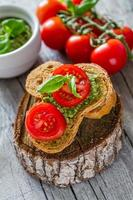 Pesto sauce in white bowl, toasts, tomatoes, garlic, cheese