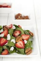 delicious spinach salad with strawberry slices and pecan nuts